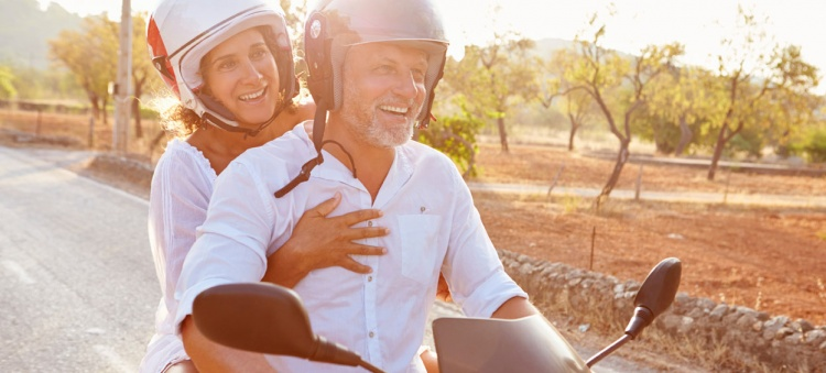Mature couple riding motor scooter